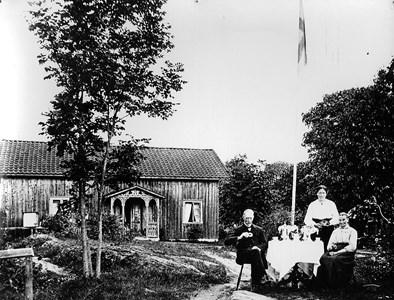 Arvidabo, Sittande f v August, Anna, och dottern Ida står vid bordet.