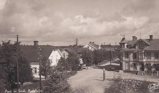 """Korsningen Storgatan - Alvestavägen. Till vänster syns Missionshuset och efter det Sjöqvists hus där det fanns skomakeri och skoaffär. Till höger syns """"Knussahuset"""". Uppkallat efter byggherren som kom från Knutsgård. Det första caféet öppnades där 1915. Jacobssons café kom 1930 och efterträddes på 60-talet av Bengt Ericsson, som bytte namnet till Centrum. Här fanns också många år Axelssons tobaksafär. Numera finns bara hyreslägenheter i huset."""